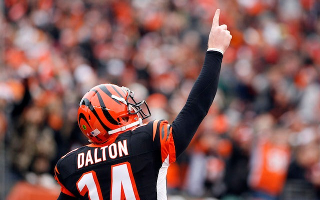 Andy Dalton is holding up one finger, which is how many playoff wins the Bengals have since 1990. (USATSI)