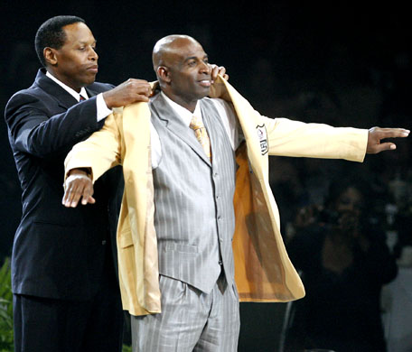 Deion Sanders receives his gold jacket from Eugene Parker at the Pro Football Hall of Fame Festival inductees dinner. (AP)