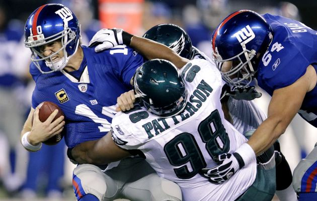 E. Manning takes the sack against Philadelphia's defense (AP).