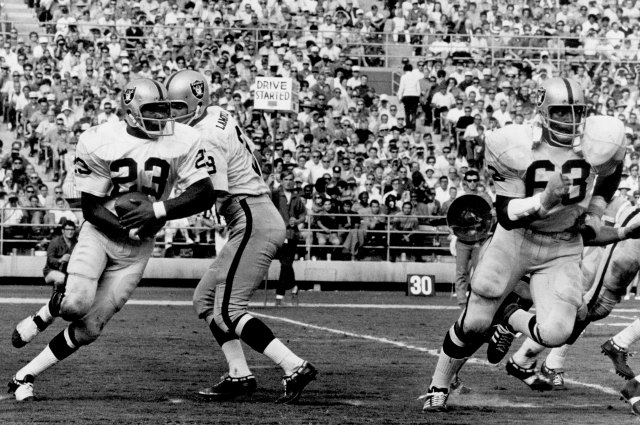 Gene Upshaw (63) is looking to knock somebody down as Daryle Lamonica hands off to Charlie Smith. (Getty Images)
