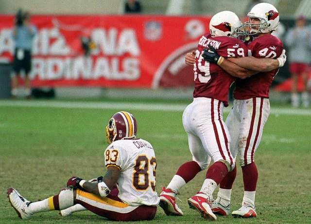 Pat Tillman celebrates with Rob Fredrickson as the Cardinals beat Washington in 2000. Albert Connell is sitting on the ground. (Getty Images)