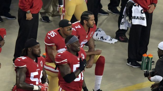 Kaepernick kneels at high school game while players protest on their backs