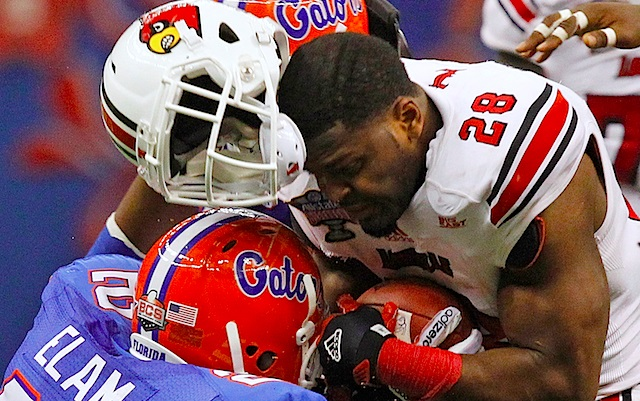 Florida's Matt Elam separates Louisville's Jeremy Wright from his helmet in January's Sugar Bowl. (AP)