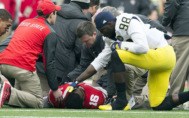 J.T. Barrett lays on the ground while Michigan's Devin Gardner checks on him.