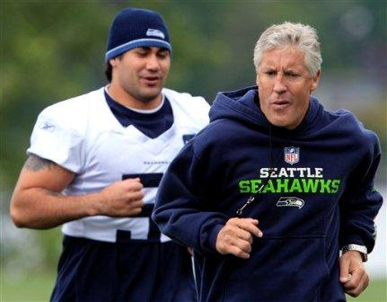 Pete Carroll, right, jogging with L. Tatupu (Associated Press)
