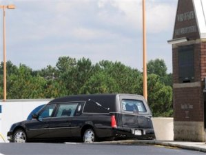 The hearse carrying the body of K. McKinley leaves after his funeral service (AP).