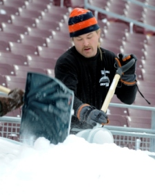 A worker tries to clear snow at TCF Bank Stadium (Getty).