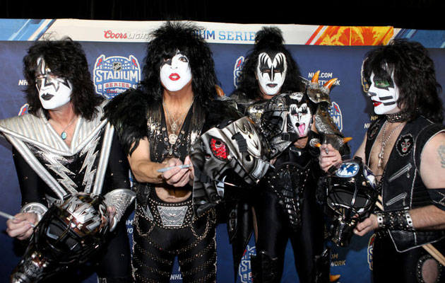 KISS autographs and poses with their custom goalie masks. (NHL)