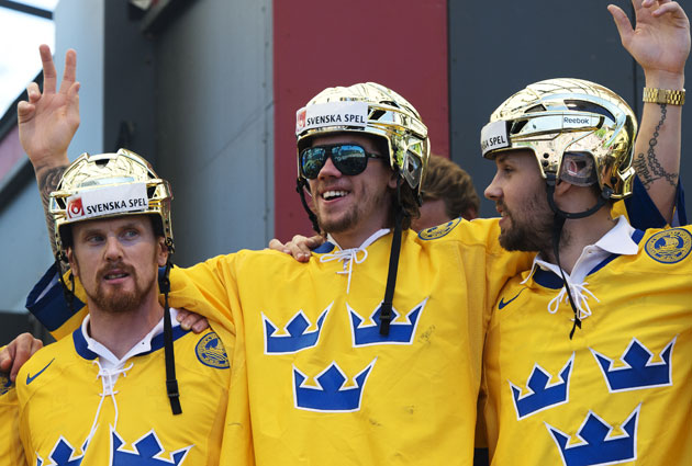 The Swedes celebrate the gold with their gold helmets in front of a large crowd. (Getty Images)