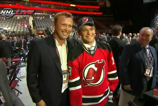 The Brouders pose for the cameras as Anthony puts on the Devils sweater. (USATSI)