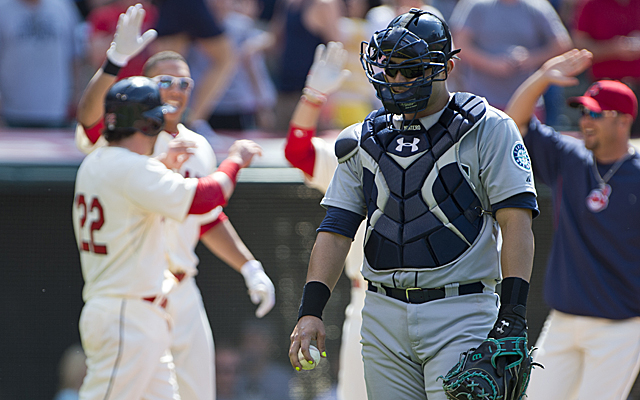 Mariners catcher Jesus Montero is disappointed while the Indians celebrate their victory.