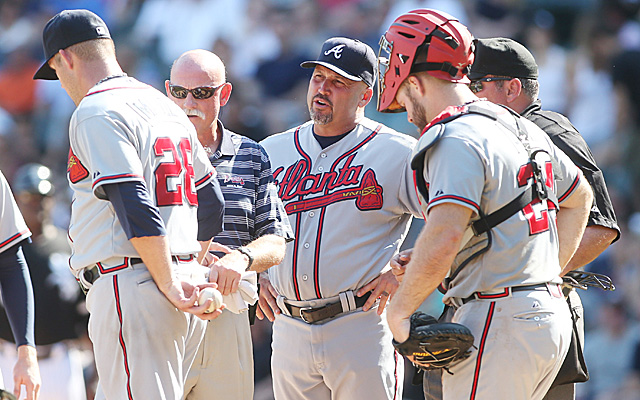 Paul Maholm discusses his injury with manager Fredi Gonzalez and an athletic trainer.