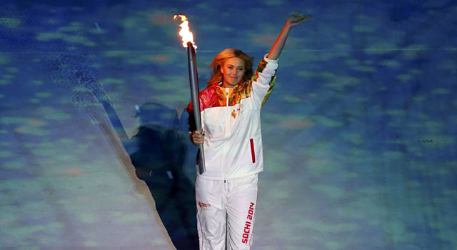 Maria Sharapova waves to the crowd as she brings the torch into the stadium. (Reuters)