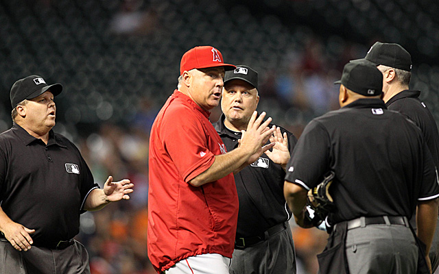 Mike Scioscia discussing the situation with the umpires Thursday in Houston.