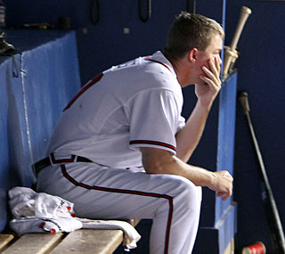 Chipper Jones sits dejected in the dugout as Atlanta's lead in the NL East dwindles.  (AP)