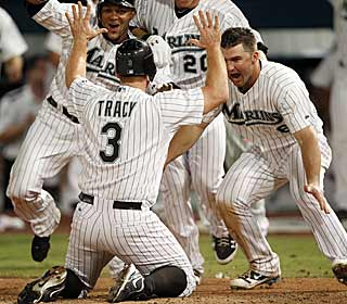 After getting his first hit as a Marlin, Chad Tracy comes around to score the game-winning run in the 10th. (AP)