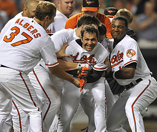 Teammates swarm Brian Roberts after the second baseman hits a rare home run in walk-off style.  (AP)