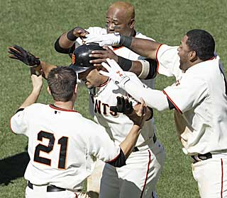 Andres Torres is given a hero's welcome after smacking a long single that clinches a win for the Giants. (AP)