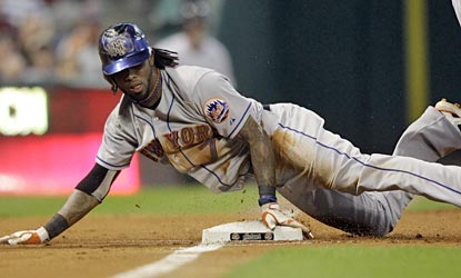 Jose Reyes slides safely into third with a triple, one of his season-high four hits on the night.  (AP)