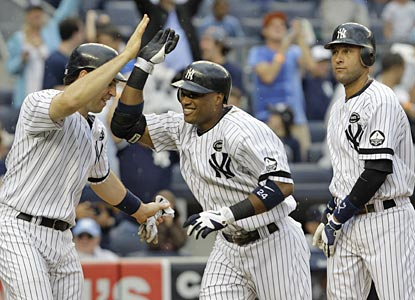Mark Teixeira and Derek Jeter greet Robinson Cano after he drives them in with a fifth-inning grand slam.  (AP)