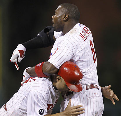 Placido Polanco restrains a heated Ryan Howard, who gets ejected in the 14th for tossing his equipment following a strikeout. (AP)