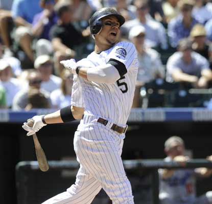 Carlos Gonzalez watches his first of two HRs fly out of Coors Field during a 10-5 win over the Dodgers. (AP)