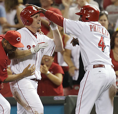 Jay Bruce, who delivers the walk-off hit, celebrates with Brandon Phillips, who represents the winning run in the 10th.  (AP)