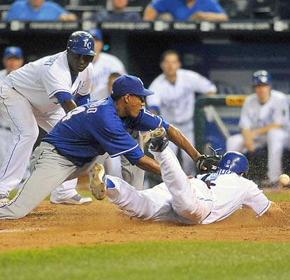 Willie Bloomquist races for home and scores in a cloud of dust on Alexi Ogando's wild pitch. (Getty Images)