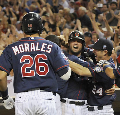 Michael Cuddyer (center) gets mobbed by teammates after he scores the winning run off a 10th-inning hit by Danny Valencia.  (AP)