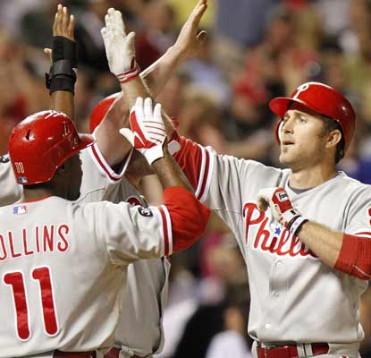 Chase Utley celebrates his grand slam  in the seventh with teammates Ben Francisco, Jimmy Rollins and Brian Schneider. (AP)
