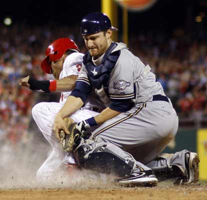 Wilson Valdez collides with Brewers catcher Jonathan Lucroy to score on a sacrifice fly in the seventh. (AP)