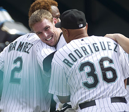 A happy Scott Cousins is hugged by Hanley Ramirez and manager Edwin Rodriguez after driving in the winning run. (AP)