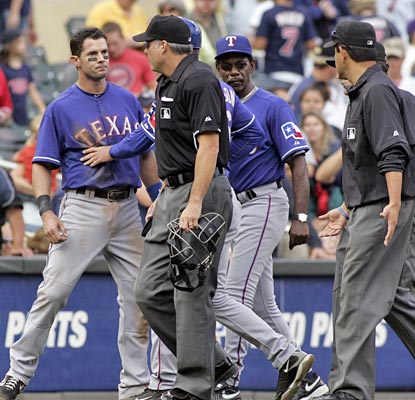 Michael Young is restrained as he argues a coach's interference call that results in the final out of the game.  (AP)