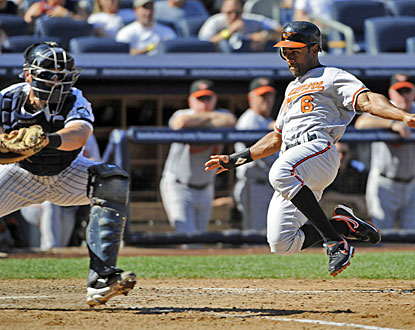 Corey Patterson slides home with the game-winning run while Yankees catcher Francisco Cervelli waits for the throw.  (AP)