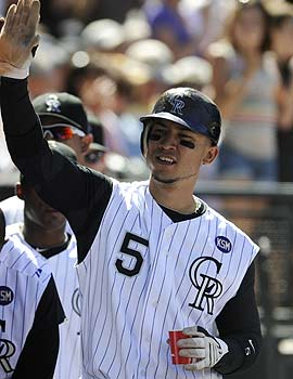 It's possible Carlos Gonzalez could high-five his way to the Triple Crown. (AP)