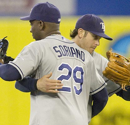 He's a team guy. Evan Longoria scores the go-ahead run and has a hug for Rafael Soriano after the win. (AP)