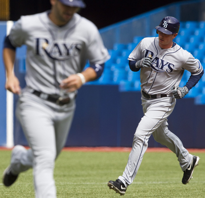 The Rays' Brad Hawpe follows teammate Sean Rodriguez around the bases on his slam off Jays' starting pitcher Ricky Romero. (AP)