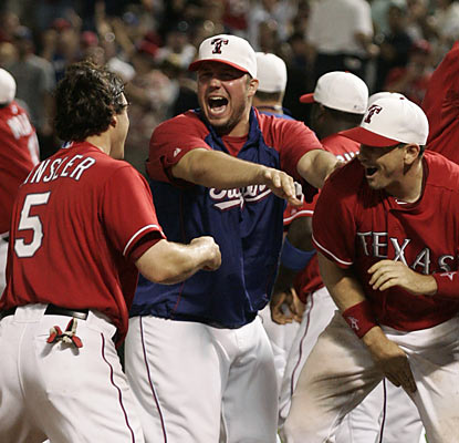 Ian Kinsler and the Rangers celebrate another walk-off win in a lengthy contest against the Yankees.  (AP)