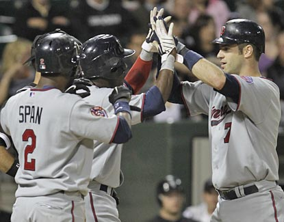 Joe Mauer is greeted at the plate by Denard Span and Orlando Hudson, the two he drives in with a three-run jack.  (AP)