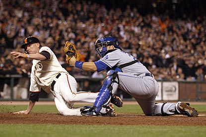 Despite Rod Barajas' effort, Aubrey Huff is safe, giving the Giants what turns out to be a much-needed insurance run.  (Getty Images)