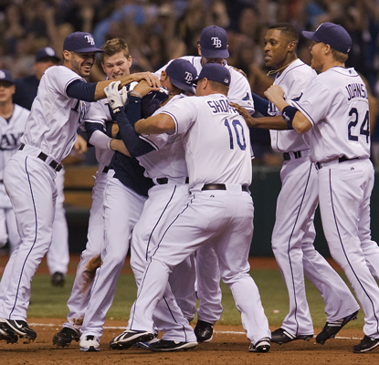 Willy Aybar is swarmed by his teammates after hitting the game-winning grounder in the 10th.  (AP)