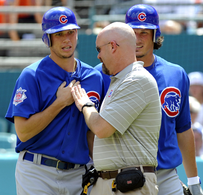 The Cubs' medical trainer checks Tyler Colvin after he was struck by a broken bat during the second inning. (AP)