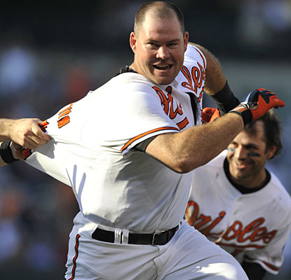 Ty Wigginton attempts to dodge his teammates after driving in the winning run for Baltimore. (AP)