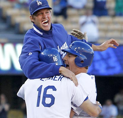 Clayton Kershaw (top) and Andre Ethier (left) mob A.J. Ellis after he delivers the game-winning single in the 11th.  (AP)