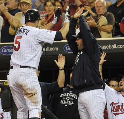 The Twins' Michael Cuddyer celebrates with his teammates after hitting a two-run shot in the sixth. (AP)