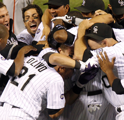 Troy Tulowitzki is mobbed by teammates after hitting a walk-off double in the 10th. (AP)