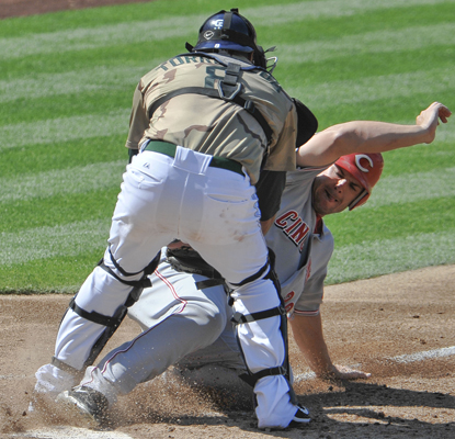 The Reds' Chris Heisey fails to score past the tag of San Diego Padres catcher Yorvit Torrealba. (AP)