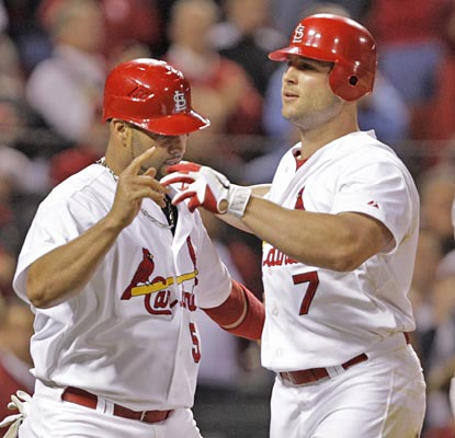 Matt Holliday is congratulated at the plate after his sixth-inning home run ties the game at 4.  (AP)
