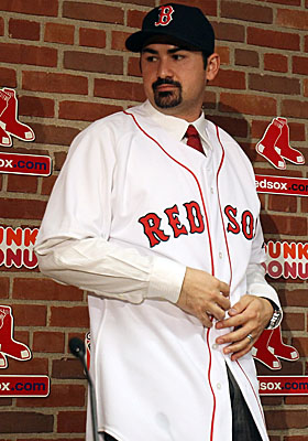 Adrian Gonzalez checks his reflection in Red Sox red and white at his official signing on Dec. 6. (Getty Images)