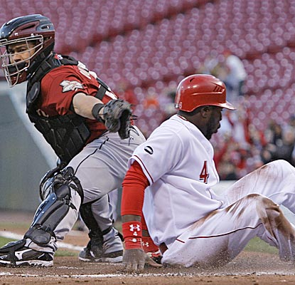 Brandon Phillips slides safely in front of the tag of Astros catcher Humberto Quintero in the first inning.  (AP)